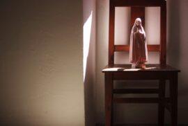Fotografia a uma cadeira com imagem religiosa em cima do tampo.