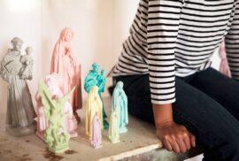 Vê-se meio corpo de uma pessoa sentada numa mesa com imagens religiosas ao seu lado.