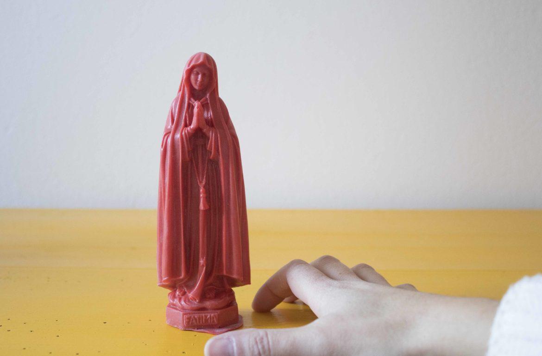 Mão a aproximar-se de uma Nossa Senhora vermelha.