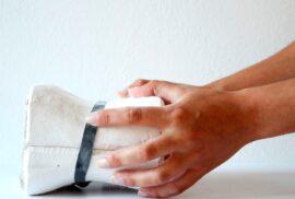Fotografia de perfil de umas mãos a agarrar num molde de gesso.