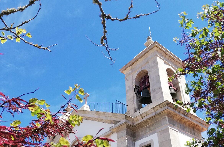 Imagem da torre de uma igreja com um sino e o céu azul.