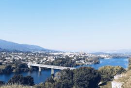 Imagem de uma paisagem com um rio e uma ponte.